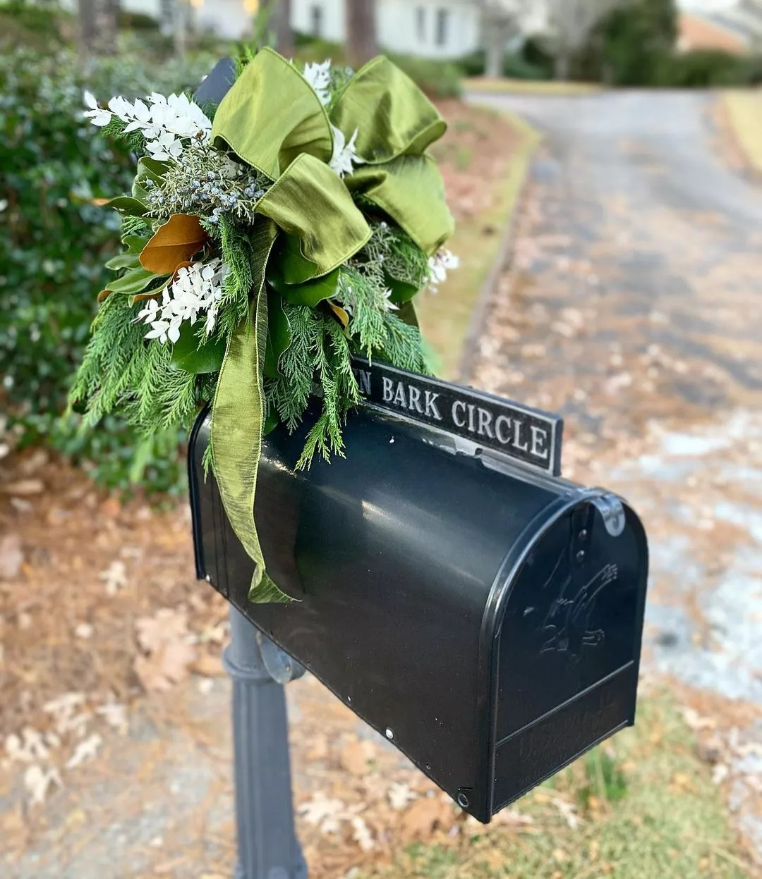 A black mailbox is decorated with a green bow, evergreen sprigs, juniper sprigs and berries, and white flowers. Photo by Instagram user @wildthingsbirmingham.