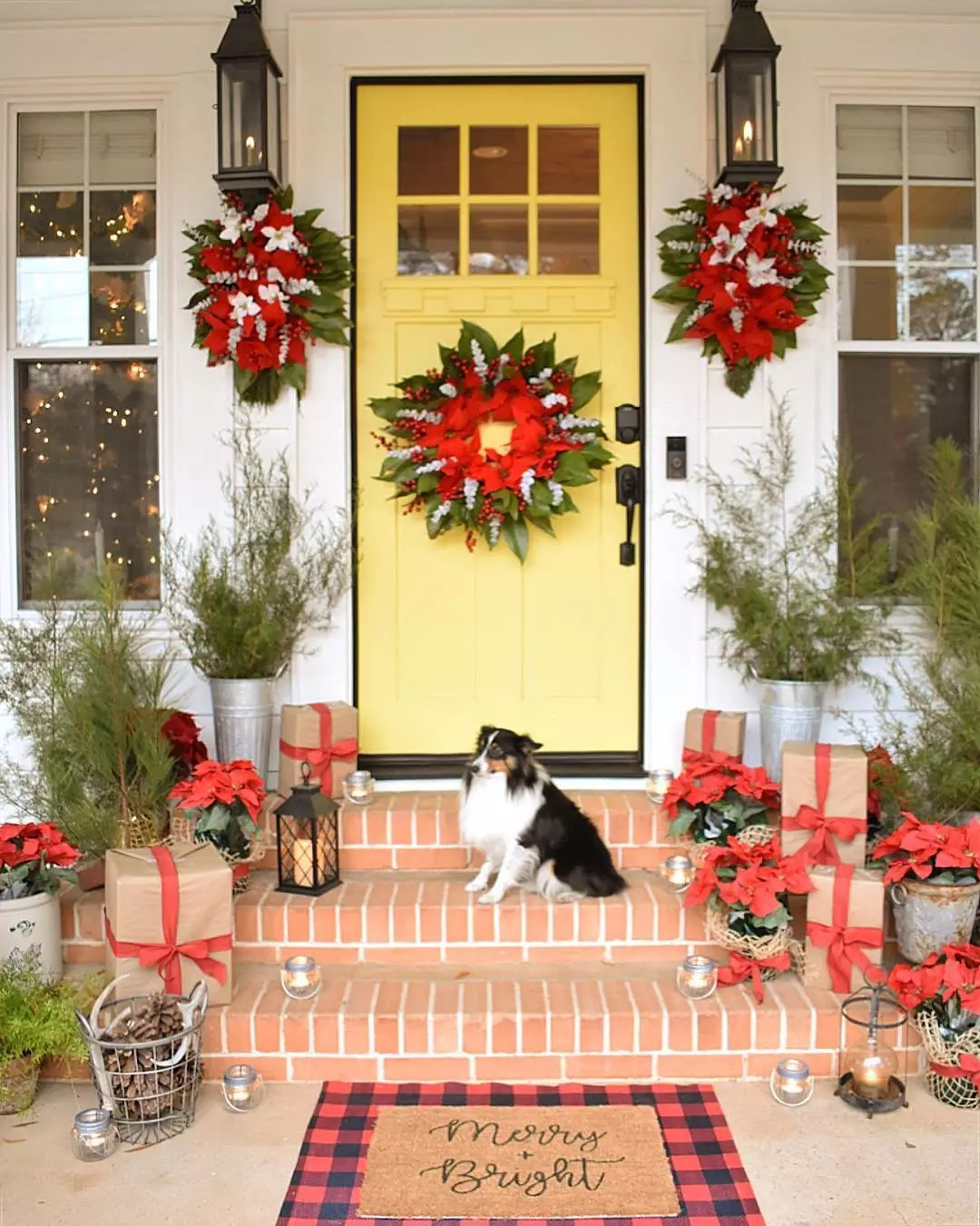 Yellow front door features a poinsetta and pine wreath, and two additional poinsettia wreathes hang from porch lanterns on either side of the door. A dog is sitting on the steps between various other planters with pine- and holiday-related decorations. Photo by Instagram user @simplysoutherncottage.
