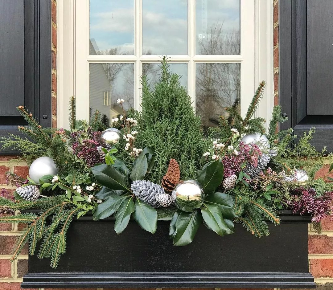 Window box stuffed with pine sprigs, cedar, cranberries, silver and regular pinecones, and gold Christmas ornaments. Photo by Instagram user @contained_creations.
