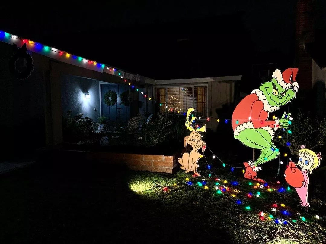 At night, a large cut out of the classic Grinch tiptoes away from the house, stealing the Christmas lights. Photo by Instagram user @kitrae.