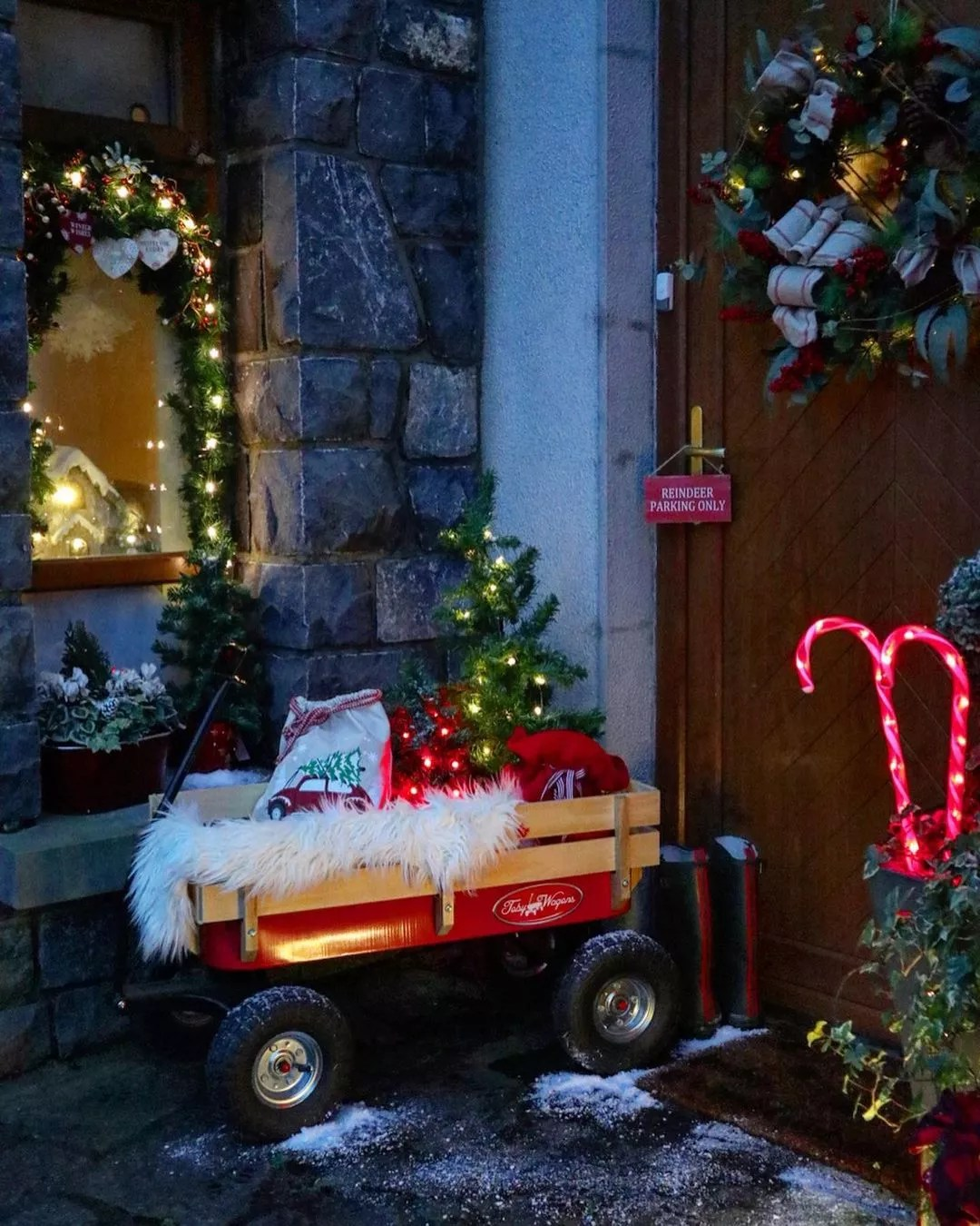 A small red and wooden wagon sits on the front porch holding a mini, lit Christmas tree, cotton material, and other various holiday decor. Photo by Instagram user @my_irish_home.