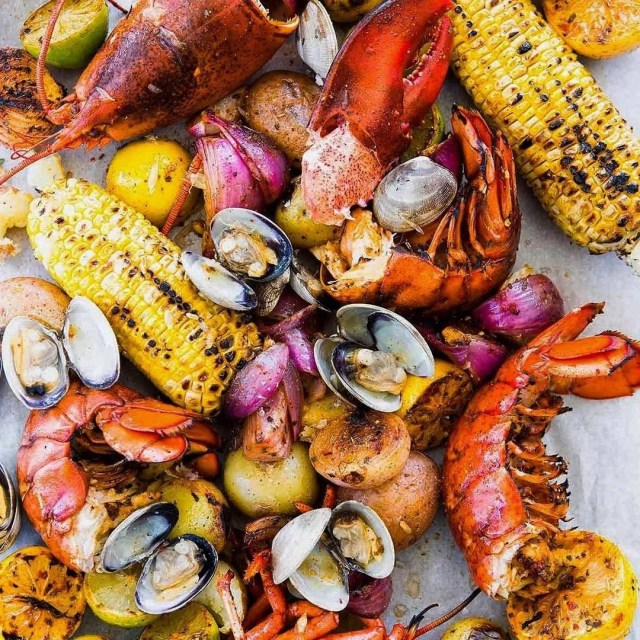 Spread of Rat's Restaurant's annual Lobster Clambake, including lobster tail and claw, corn-on-the-cob, clams, and potatoes. Photo by Instagram user @rats.restaurant