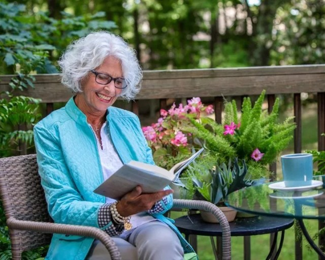 Older Woman Sitting on Her Deck Reading a Book. Photo by Instagram user @brookdaleliving