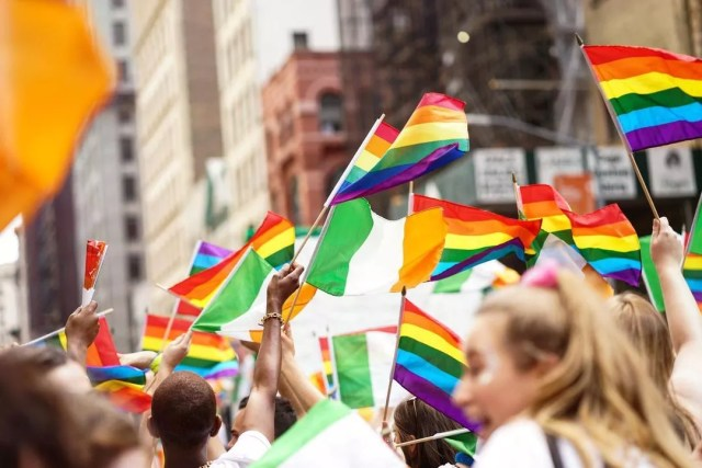 People Waving Rainbow Flags Walking in the NYC Pride Parade. Photo by Instagram user @nycpride