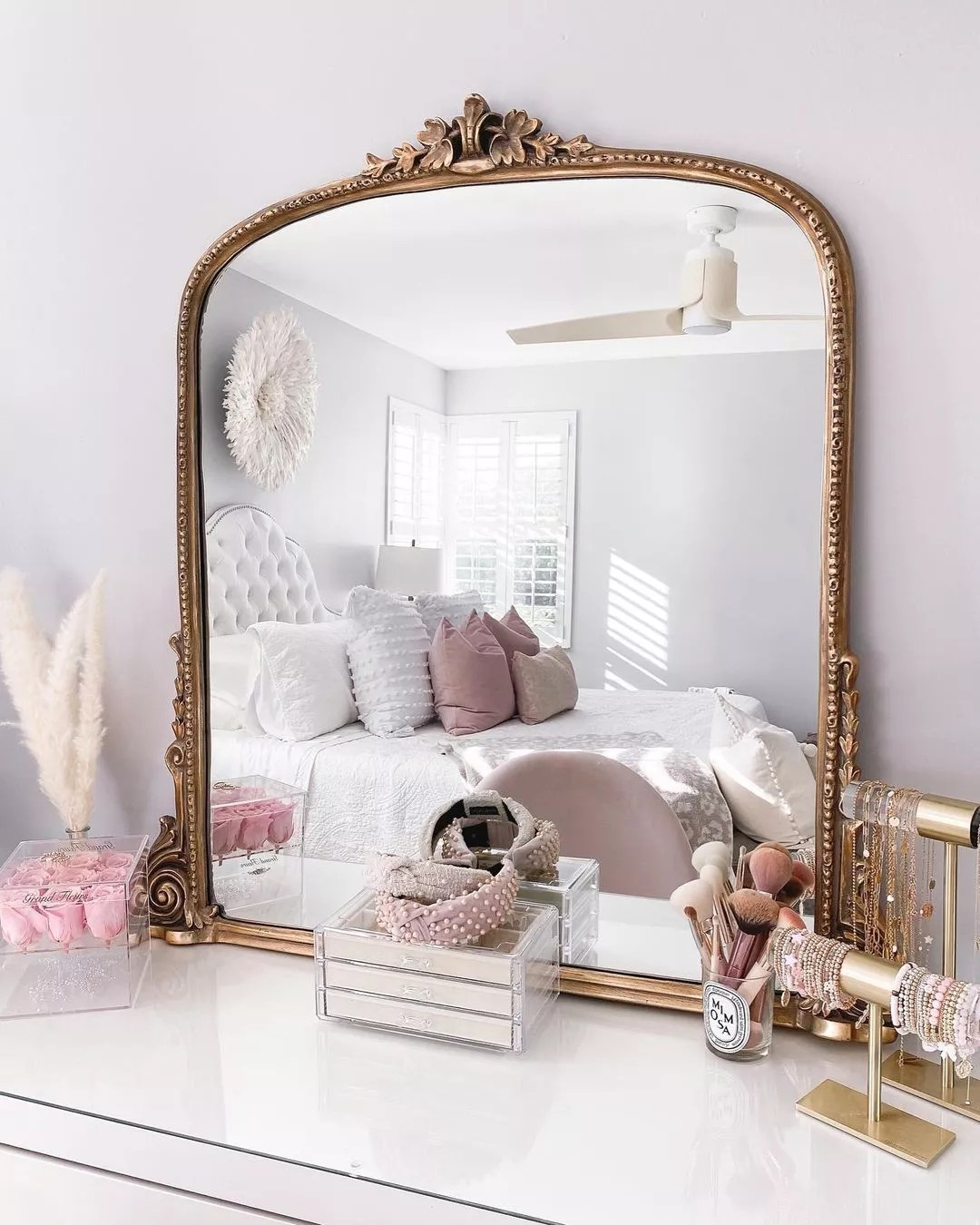 Large mirror with decorative brass finish sitting on dresser. Photo by Instagram User @fancythingsblog