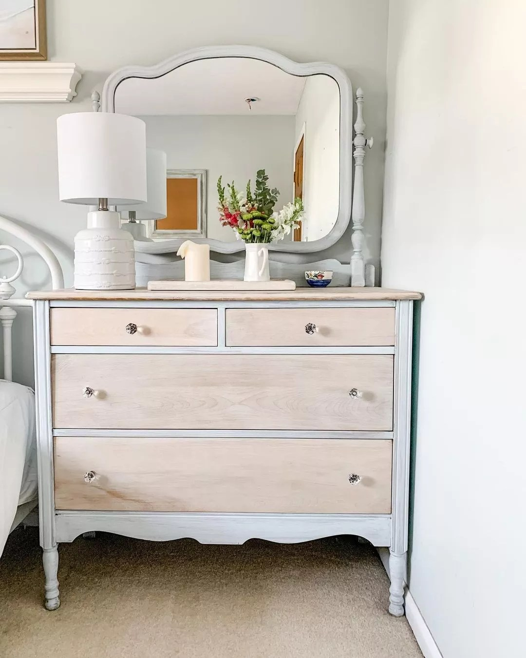Wooden dresser with light finish next to bed. Photo by Instagram User @mybeachyfarmhouse