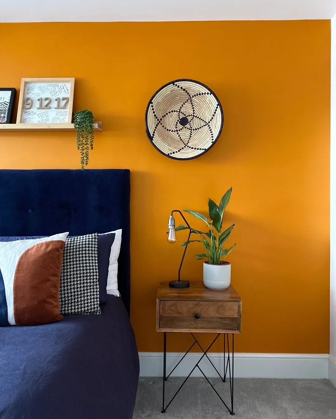 Deep navy bed against a bright orange wall. Photo by Instagram user @mushahome.