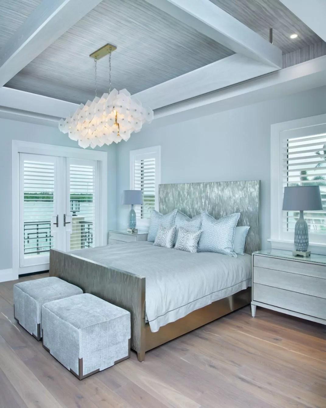 Photo of large, open bedroom with light hardwood floors and sky blue walls. Photo by Instagram user @ illuminateddesign_naples.