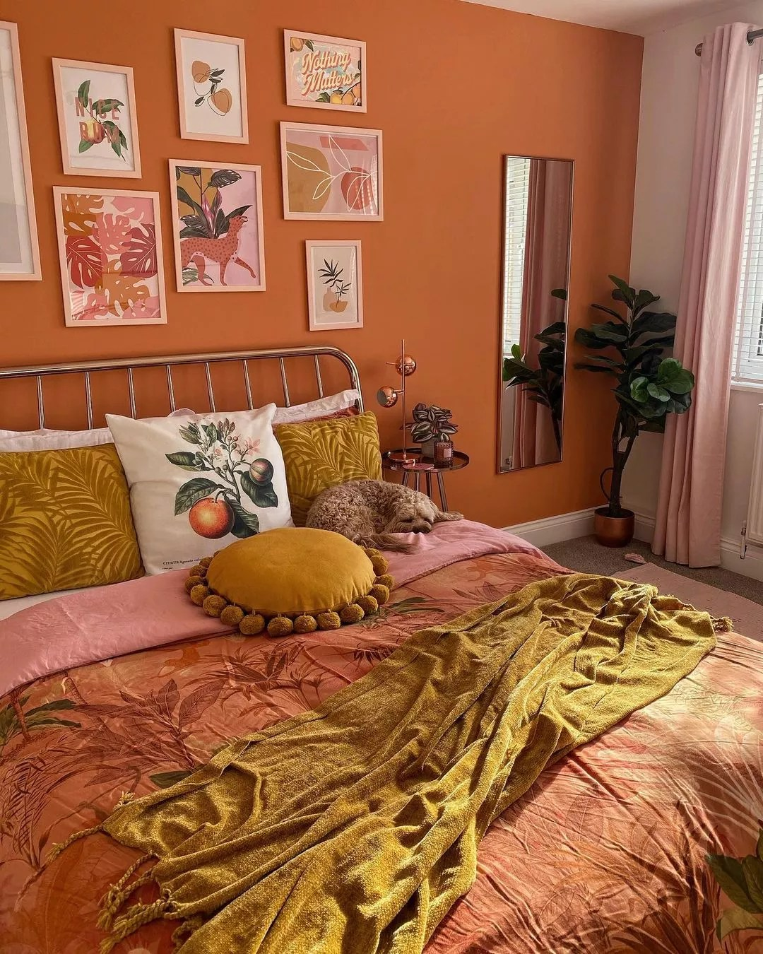 Bright room of orange colors, the focus of which is the terra cotta wall behind the bed. Photo by Instagram user @atnumbersixtyeight.