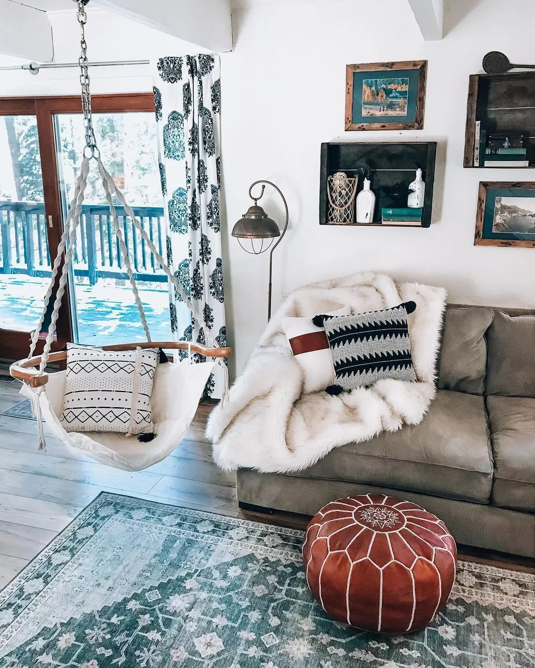Living room with cool touches, including a dark teal rug, teal and navy-patterned curtains, and soft grey sofa, beside a hanging chair made of wood, white canvas material. Photo by Instagram user @shoppingwith.hannah.