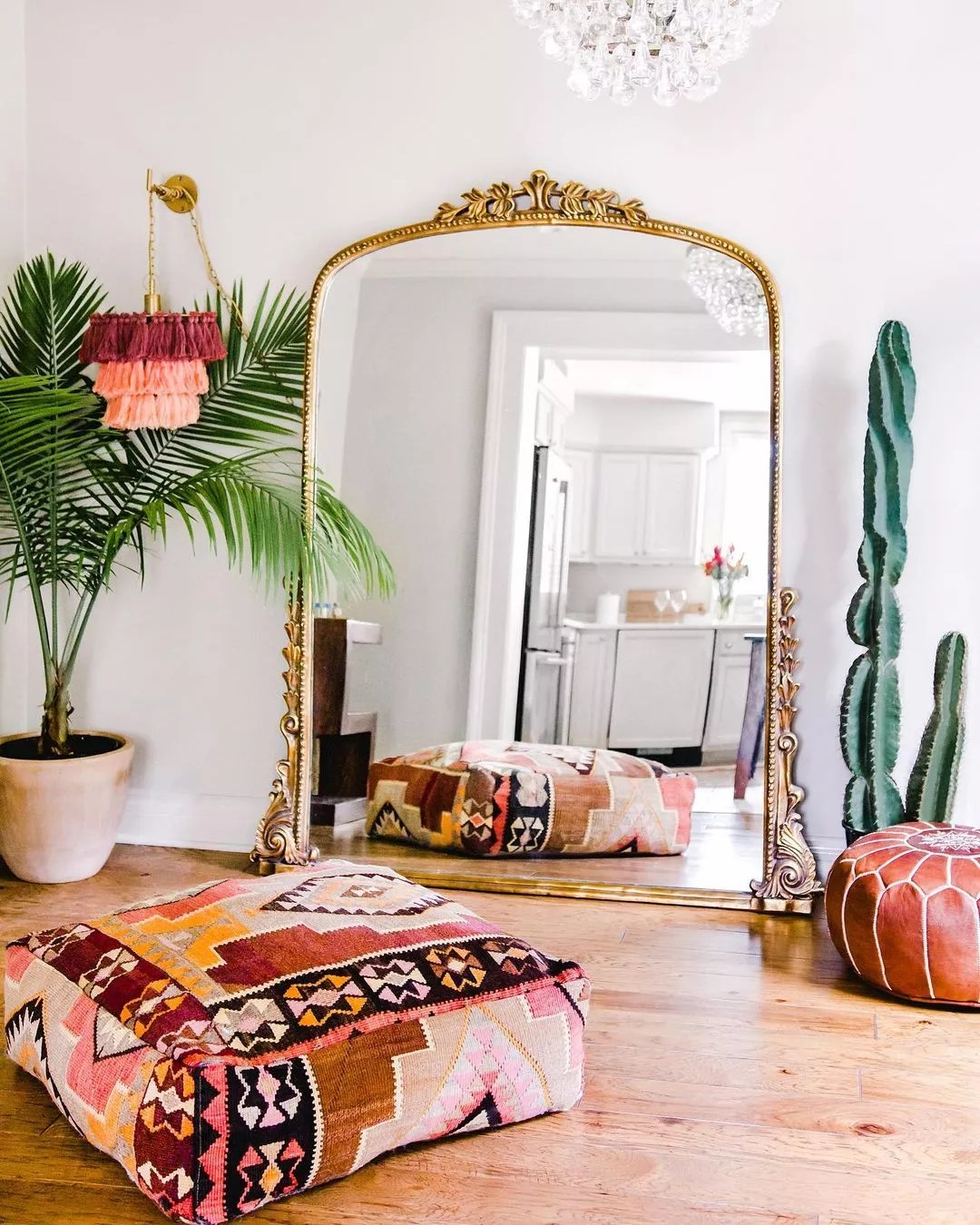 Southwestern-patterned pouf sits in front of a wide floor mirror, which is framed with gold filigree. Photo by Instagram user @alysestudios.