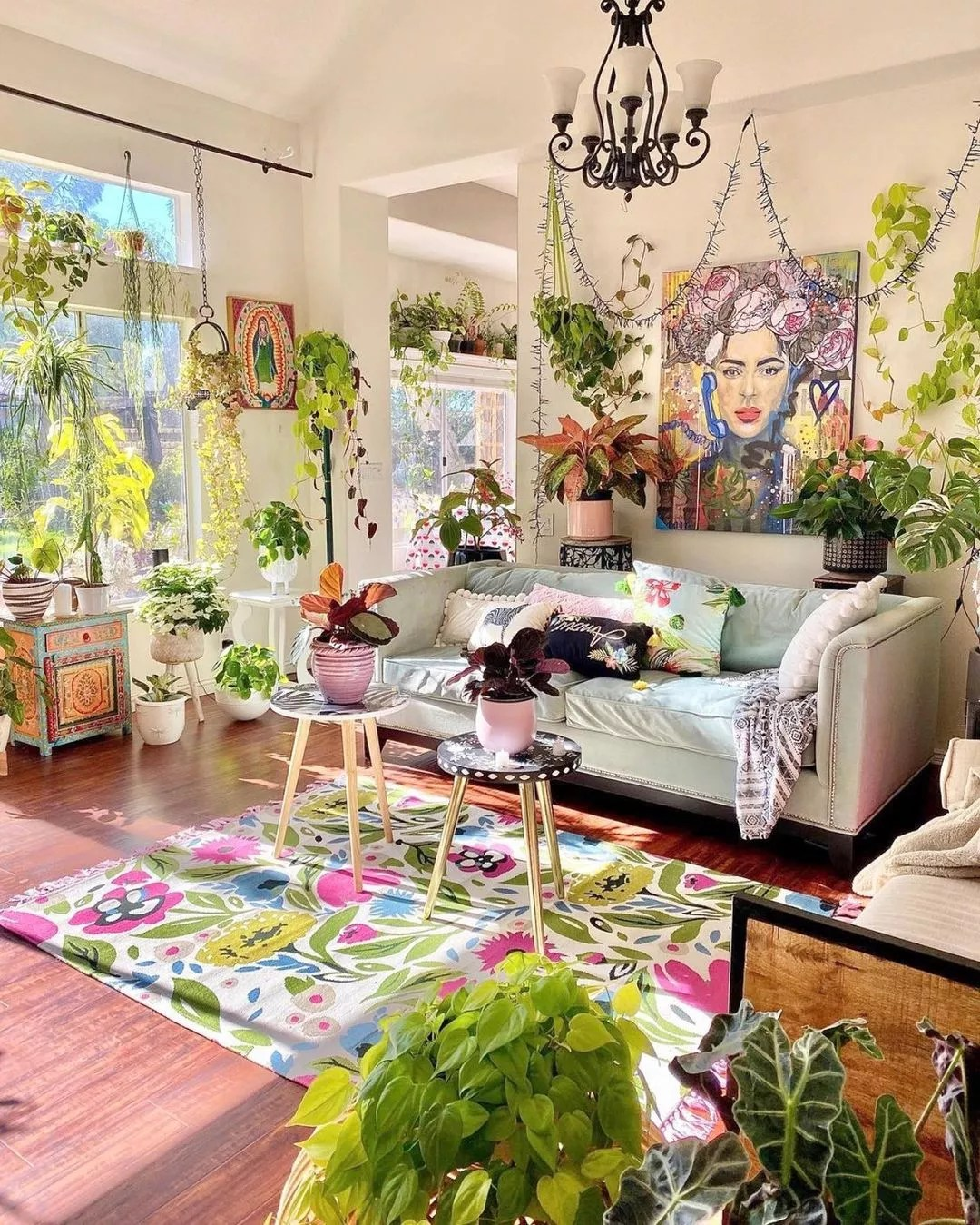 Open livingroom with several windows, high ceilings, and over 20 plants, including a pathos, English Ivy, spider plant, and Monstera. The room rug features bright, simple flowers and leaves.