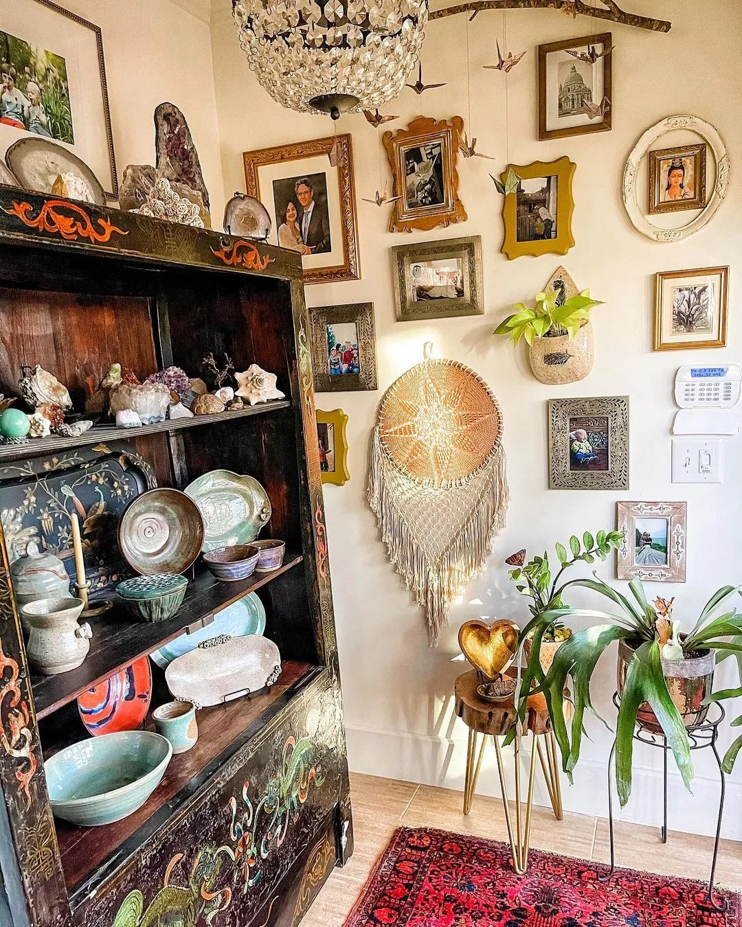 Decorated, antique bookshelf presenting vintage platters, pots, shells, and geods, beside plants and a wall with photos framed in old, unique frames. Photo by Instagram user @the.rustic.bohemian.