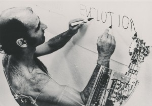 Human with robot exoskeleton arm, writing Evolution