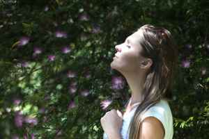 Person meditating near a tree with flowers