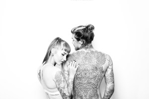 Caucasian woman grabbing a caucasian man's arm and back that is covered in tattoos.