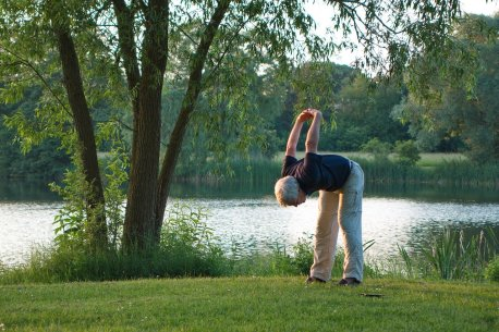 Older man with white hair in the park bending over with hands behind back