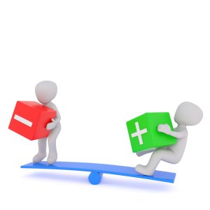 balance with two cartoons, on one side one holding a negative block and the other holding a positive block.