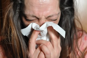 middle aged caucasian woman blowing her nose into a tissue.