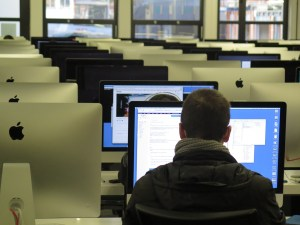 man sitting in front of a computer in a room filled with computers.