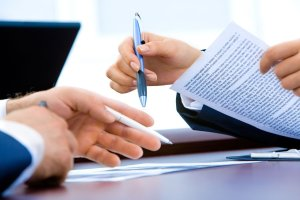 two hands with pens in them pointing at paperwork.