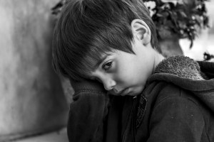 black and white picture of a little boy that is sad