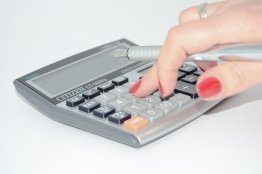 caucasian womans hand holding a pen in her hand pressing a number on a calculator