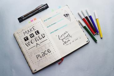 "journal open with ""make the world a better place"" written in it with different color markers on the table next to it."