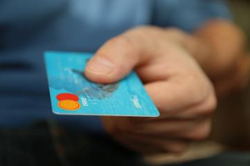 caucasian hand holding a blue credit card.