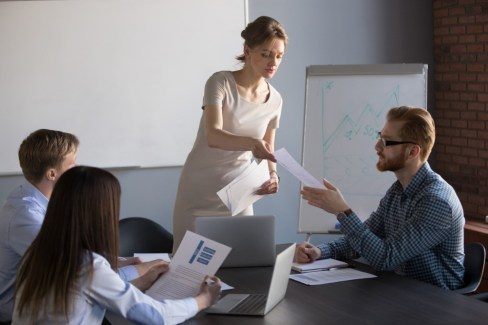 caucasian woman standing and handing a caucasian man a piece of paper in an office room setting with other people sitting at the desk