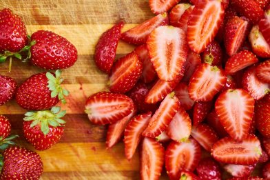 strawberries on a chopping block with them split in half