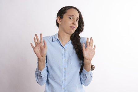 caucasian woman with her hair in a side braid holding both of her hands up as to say no.