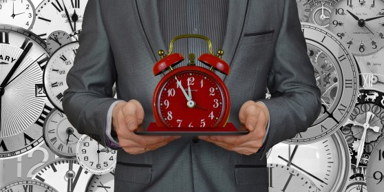 man in a gray suit holding up a red alarm clock