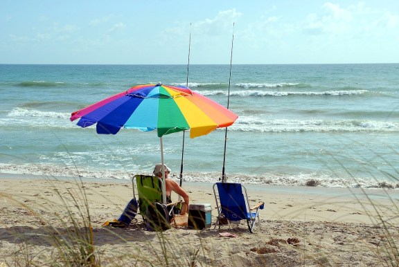 man sitting on a beach under a rainbow umbrella with fishing pole in the sand