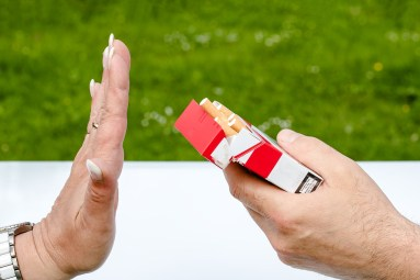 woman's hand rejecting a pack of cigarettes in a man's hand.