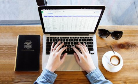 hands on a keyboard of laptop with a spreadsheet on the screen