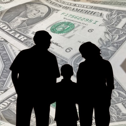 silhouette of people holding hands with a child in the middle and money bills as the background.