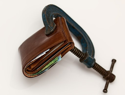 wallet with a black wrench squeezing it