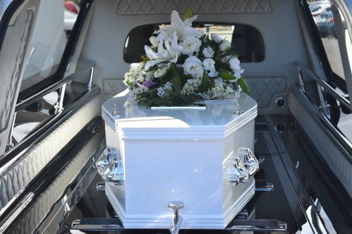 white casket in a car with white flowers on top of it