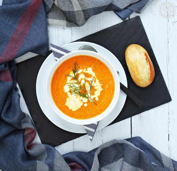 Tomato, Carrot and Dill Soup served on a slate platter with a bread roll.
