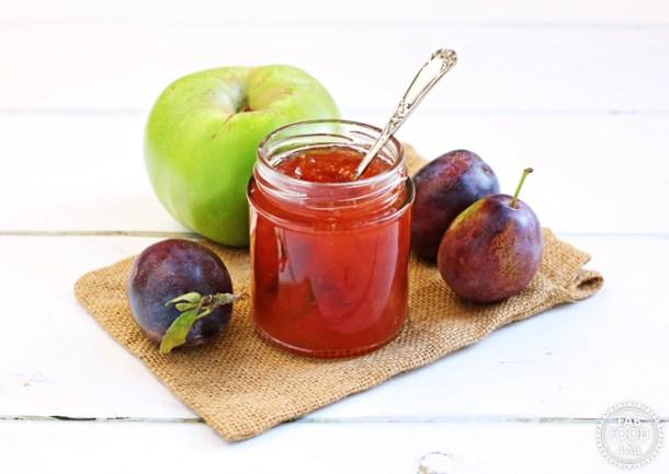 Plum & Apple Jam in open jar with teaspoon flanked by Marjorie plums & a Bramley apple.
