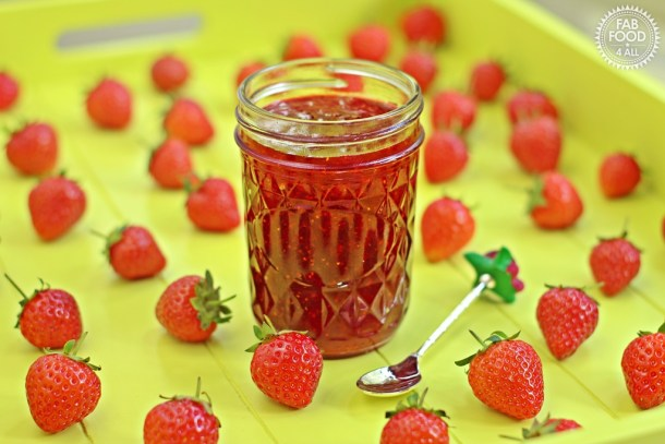 Quick One Punnet Strawberry Jam in jar with a teaspoon and scattered strawberries.