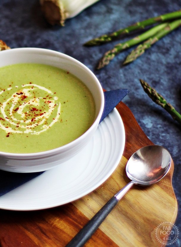 Cream of Asparagus & Celery Soup on a wooden board surrounded by asparagus, celery and onion.