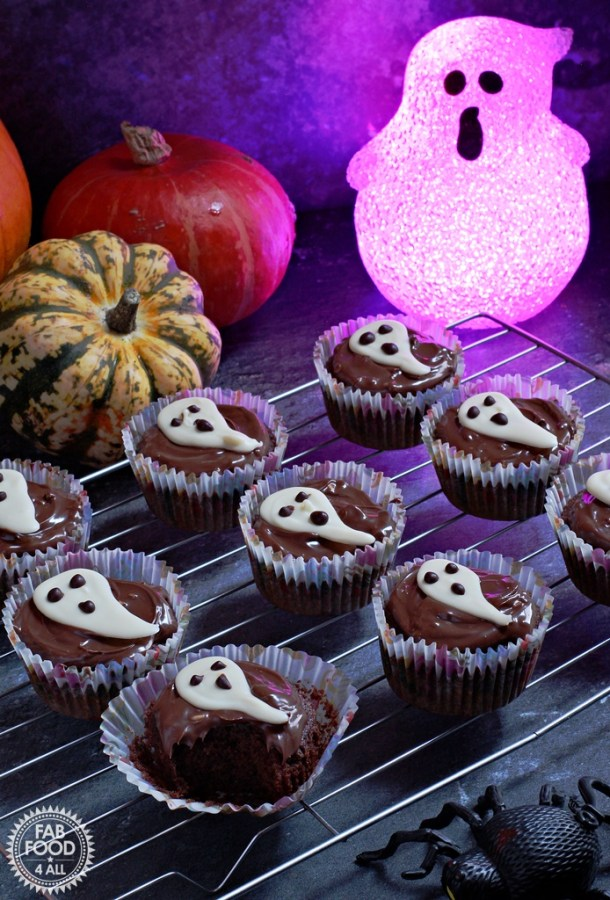Easy Halloween Ghost Cupcakes - delicious chocolate & coffee flavoured sponge topped with chocolate spread & a handmade white chocolate ghost. Ghost and pumpkin background.