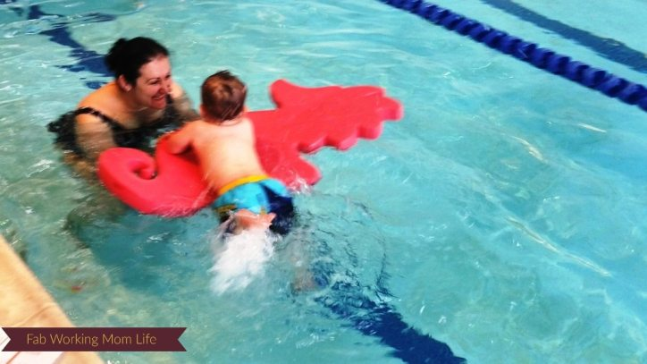 Baby H kicking while holding onto a seahorse floatie.