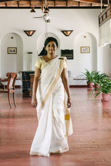 A beautiful young Indian woman dressed in a traditional cream with gold trim Keralan sari walks gracefully across the terra cotta tiled lobby of the CGH Earth hotel Brunton Boatyard in Fort Kochi, Kerala.