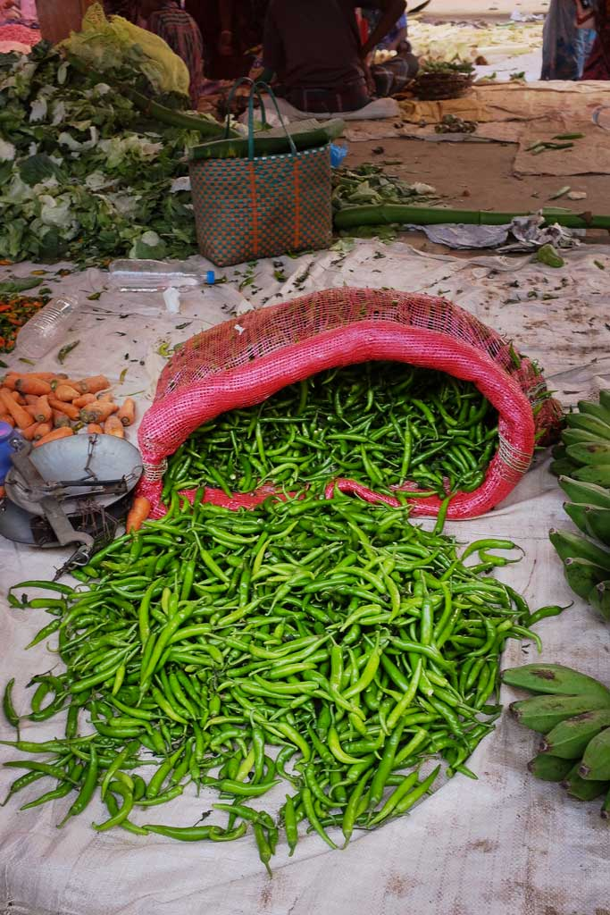 Long green chillies spill out of a red bag sitting open on white tarp laid on the ground in a vegetable market outside of Madurai.