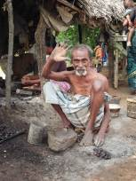 A shirtless, elderly South Indian man wearing a light coloured dhoti squats on the ground with his knees near his shoulders as he waves open-palmed to the camera. Unshelled roasted cashews and a grinding stone sit at his feet.