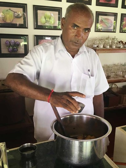 Raman, pastry chef at The Bangala Hotel in Karaikudi looks up at the camera as he adds a tasty ingredient to a large pot.