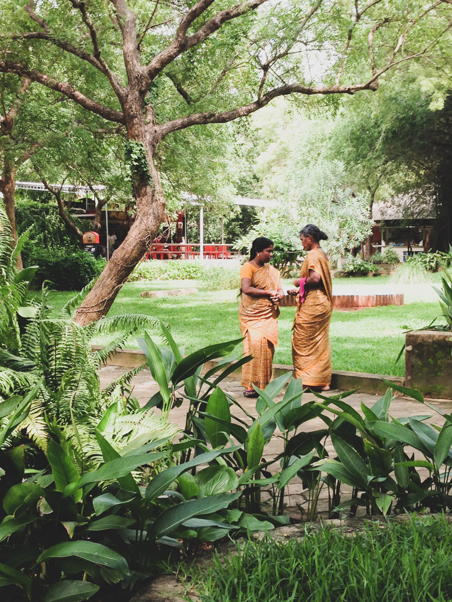 Two women in saffron coloured saris at Auroville - City of Dawn, South India.